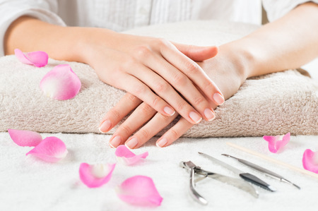 Closeup shot of female hands with french manicure on a towel surrounded by petals and manicure set. Woman getting nail manicure. Shallow depth of field with focus on woman hand. Stock Photo