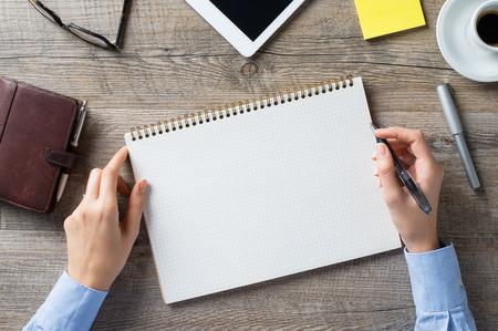 手帳にメモを取る女性のクローズ アップ ショット。ビジネスの女性は、彼女の事務所の日記で書いています。独自のメッセージを記述する空白のペ