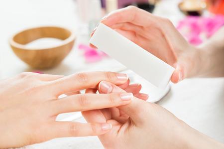 manicura: Primer disparo de una mujer en un salón de belleza recibe una manicura por una esteticista en el salón de uñas. Mujer que usa un buffer para el clavo archivo. Poca profundidad de campo con enfoque en lima.