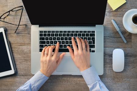 mecanografía: Primer disparo de una mujer escribiendo la mano en el teclado de su ordenador portátil. La muchacha se está trabajando en la oficina en la computadora. Concéntrese en escribir en el teclado de la computadora portátil.