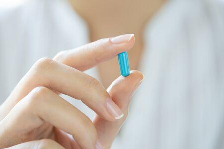 vitamina a: Primer disparo de una mujer que muestra azul cápsula de la píldora. Mano femenina que sostiene una medicina. Poca profundidad de campo con enfoque en azul cápsula de la píldora.