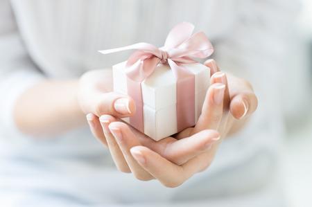 sorpresa: Cierre de tiro de las manos femeninas que sostienen un pequeño regalo envuelto con cinta de color rosa. Pequeño regalo en las manos de una mujer cubierta. Poca profundidad de campo con enfoque en la cajita.