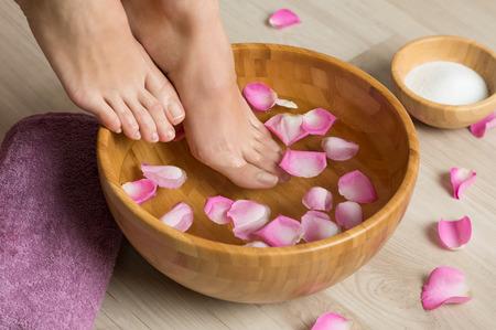 Gros plan d'une femme tremper les pieds dans l'eau avec des pétales dans un bol en bois. Jolis pieds féminins au salon de spa sur la procédure de pédicure. Faible profondeur de champ avec un accent sur les pieds.