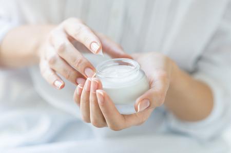 mujer maquillandose: Primer disparo de manos que aplican la crema hidratante. Mujer de la belleza que sostiene un frasco de vidrio de crema para la piel. Poca profundidad de campo con el foco en la crema hidratante. Foto de archivo