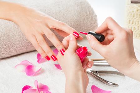 Plan Gros plan d'une esthéticienne appliquer le vernis à ongles à ongles femme dans un salon de manucure. Gros plan d'une main de femme avec du vernis à ongles rose après la manucure.