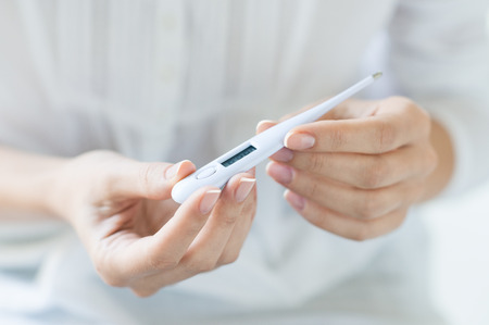 Closeup shot of a woman looking at thermometer. Female hands holding a digital thermometer. Girl measures the temperature. Shallow depth of field with focus on thermometer.