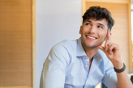 Close-up shot van jonge man glimlachend en opzoeken. Knappe jonge man lacht en kijkt weg. Portret van de mens denken en beeldvorming. Contemplatieve man met overhemd denken en lachend over de toekomst.