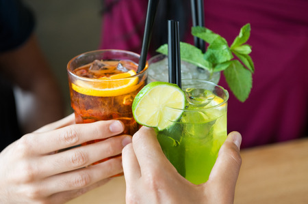 aperitif: Closeup shot of friends toasting with cocktails. Young people drinking at aperitif. Shallow depth of field with focus on friends hand toasting juice glass. Close up of hands holding a cocktail glass. Stock Photo