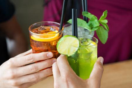 Gros plan des amis de grillage avec des cocktails. Les jeunes à boire à l'apéritif. Faible profondeur de champ avec un accent sur le verre de jus de grillage amis de main. Gros plan des mains tenant un verre à cocktail. Banque d'images