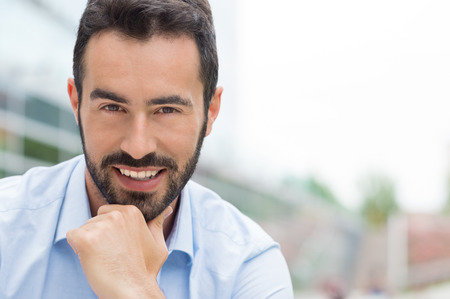 Closeup shot of young man with hand on chin smiling. Successful businessman looking at camera. Portrait of proud guy with beard looking at camera outside with copy space.