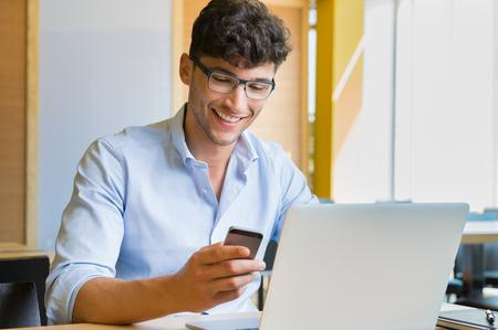 Close-up shot van een jonge man het typen van een tekst op de mobiele telefoon. Kerel die een moderne smartphone en het schrijven van een telefoon bericht. Glimlachend jonge zakenman die mobiele telefoon met de laptop op tafel bij coffee bar.