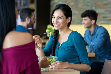 latinas: Closeup shot of young women eating salad at restaurant. Happy female friends smiling and chatting. Portrait of smiling girl holding a forkful of salad during lunch break.