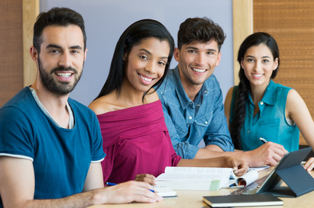 student studying: Closeup shot of young men and women studying. Portrait of happy student smiling and looking at camera. A team of students sitting in a row behind the table. Stock Photo
