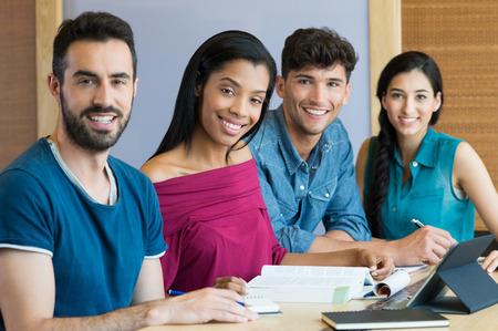 estudiando: Primer disparo de los hombres y mujeres que estudian j�venes. Retrato de estudiante feliz sonriendo y mirando a la c�mara. Un equipo de estudiantes que se sientan en una fila detr�s de la mesa. Foto de archivo