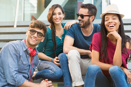 Closeup shot of young friends sitting on staircase having fun. Happy girls and guys smiling and looking at camera. Young men and young women stay together. Stock Photo