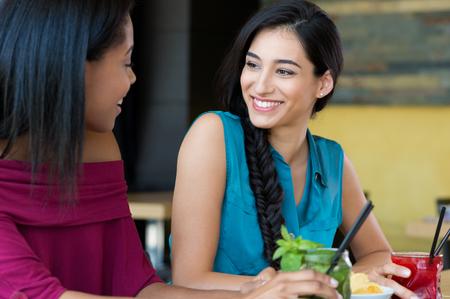 jovenes tomando alcohol: Primer tirado de la mujer sonriente que sostiene joven c�ctel. Dos amigos femeninos sonrientes y beber c�cteles en la hora feliz. Retrato de la hermosa joven en el chat durante el c�ctel.