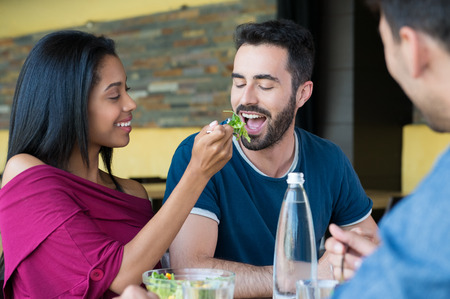 eating salad: Closeup shot of young woman feeds salad to her boyfriend. Friends having meal together. Happy young friends eating salad at restaurant. Stock Photo