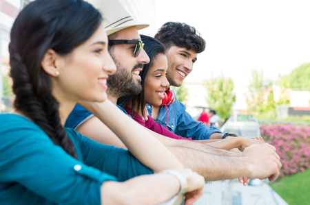 Closeup shot of young friends leaning on railing. Happy friends smiling ina row. Portrait of happy girls and guys in a row thinking about their future. Stock Photo