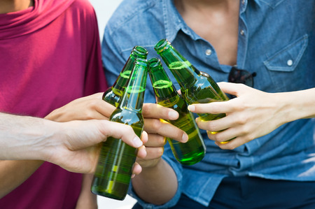 toast: Closeup shot of happy friends toasting with bottles of beer. Girls and guys drinking beer outdoor in a summer day. Close up of female and male hand holding a bottles of beer. Stock Photo
