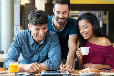 prima colazione: Colpo del primo piano di giovani amici felici che per mezzo digitaltablet durante la colazione. Uomini sorridenti e donna che fanno colazione al bar. Felice giovani amici guardando palmare e con una colazione gioiosa.