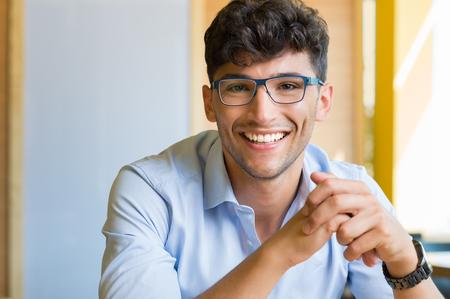 persona feliz: Primer disparo del joven hombre que llevaba gafas. Retrato de un hombre con camisa y gafas mirando a la cámara interior. Hombre joven sonriente hermoso que desgasta azul espectáculo. Foto de archivo