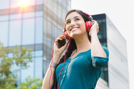 city center: Closeup shot of young woman listening to music with mobile phone in the city center. Happy smiling girl listening to music with professional red headset. Beautiful brunette young woman feeling free and thinking.