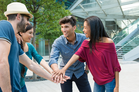 huddling: Closeup shot of young friends making huddle with their hand. Happy smiling friends. Happy young friends making huddle. Portrait of a group of people with their hands stacked in a city center. Stock Photo
