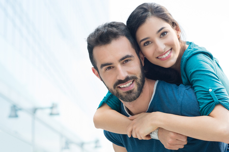 Closeup shot of young man carrying young woman on his back. Happy smiling couple looking at camera. Happy couple putdoor having fun piggyback in love. Standard-Bild