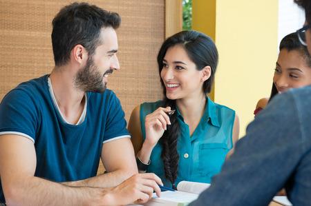 colegios: El primer tiró de hombre joven y una mujer que discute en la nota. Estudiantes sonrientes felices que se preparan para el examen. Individuo y muchacha sonriente y mirando el uno al otro mientras estudiaba.
