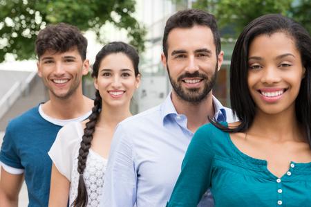 Detailní záběr mladých přátel stojí v řadě venku. Šťastné skupina mužů a žen s úsměvem a díval se na kameru. Šťastní mladí přátelé venku.