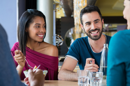 people eating restaurant: Closeup shot of young woman and man having meal. Happy smiling multiethnic friends eating at restaurant. Shallow depth of field with focus on young friends eating meal.