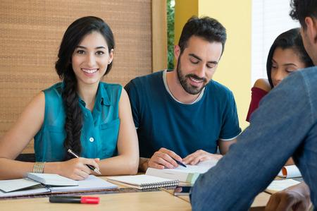 hispánský: Detailní záběr na mladé ženy při pohledu na fotoaparát při studiu se svými přáteli v knihovně. Portrét studentka příprava na exam.Beautiful mladé ženy při pohledu na fotoaparát. Reklamní fotografie
