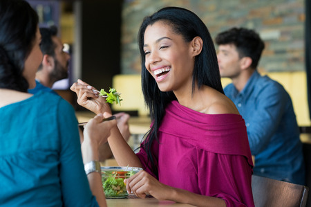 african women: Closeup shot of young woman eating salad with her friend. African girl smiling at lunch. Lughing woman eating salada at restaurant during her lunch break.