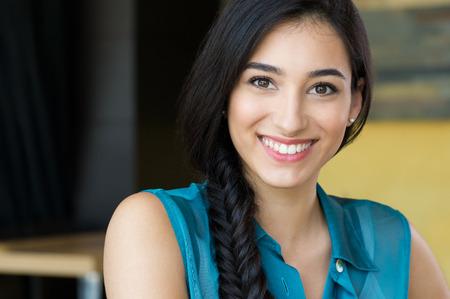 Close-up shot van jonge vrouw lachend. Portret van brunette meisje op zoek naar de camera en lacht. Ondiepe scherptediepte met focus op mooie jonge gelukkig meisje met vlecht glimlachen. Stockfoto