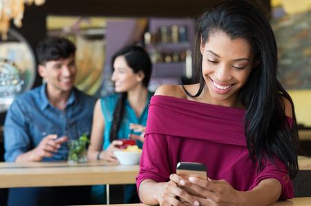 mujeres negras: Retrato de la mujer africana mensajes de texto en el móvil en la cafetería y riendo. Muchacha sonriente sosteniendo un teléfono inteligente y la escritura. Mujer joven feliz sentado en el bar de café y mirando a su teléfono con una gran sonrisa.