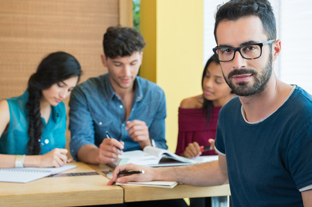 student: Closeup shot of young man looking at camera. Male student preparing university exam. Shallow depth of field with focus on handsome young man making note. Portrait of guy with eyeglasess with others students studying in background.