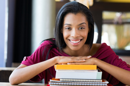 shallow  focus: Closeup shot of young woman lies on stack of books. Happy female student smiling and looking at camera. Shallow depth of field with focus on young african woman rests on stack of books.