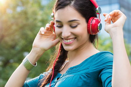 Closeup shot of young woman listening to music in a park. Portrait of happy smiling girl feeling free with music. Close up face of beautiful latin girl listening to music with professional headphone and dancing in a city center. Banque d'images