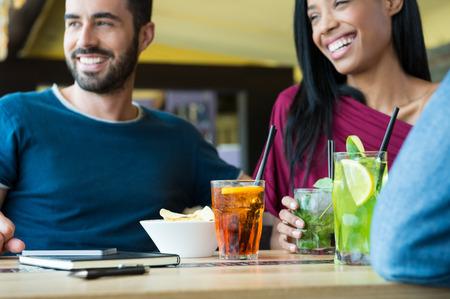 bebidas alcoh�licas: El primer tir� de hombre joven y una mujer con un c�ctel. Amigos que beben bebidas alcoh�licas en la fiesta de coctel. Poca profundidad de campo con enfoque en copas de c�ctel en la mesa.