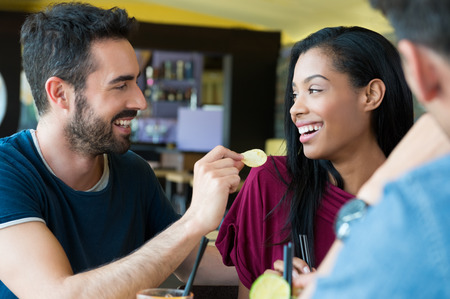 aperitif: Closeup shot of young man feeds potato chip to young woman. Friends smiling and looking eachother. Portrait of happy girl and guys stand together at bar. Stock Photo