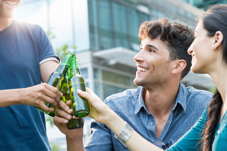 cheer: Closeup shot of young friends toasting with bottles of beer. happy smiling guys and women drinking beer outdoor. Carefree group of people cheers with beer at sunset. Stock Photo