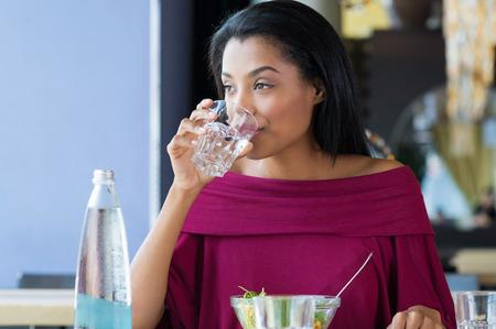 alimentos y bebidas: Primer tirado de la mujer joven que bebe un vaso de agua. Niña africana agua potable durinh su pausa para el almuerzo en el restaurante. una bebida Hermosa chica sedienta un vaso de agua y mirando a otro lado.