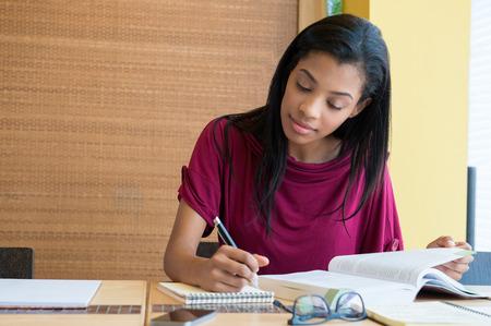 estudiantes: Primer tirado de la mujer joven que toma abajo de la nota en el diario. Estudiante femenino preparar nota para el examen. Muchacha concentrada estudiando en un libro y tomando nota abajo sentado en el escritorio.