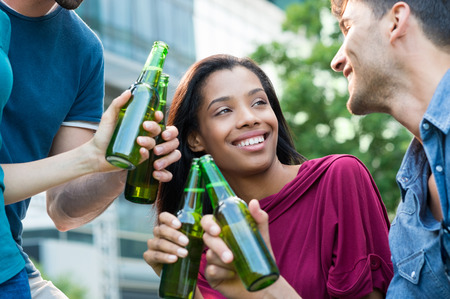 youth group: Closeup shot of young friends toasting with bottles of beer. Multiethnic people drinking beer. Happy mem and women smiling and drinking a beer for the aperitif. Stock Photo