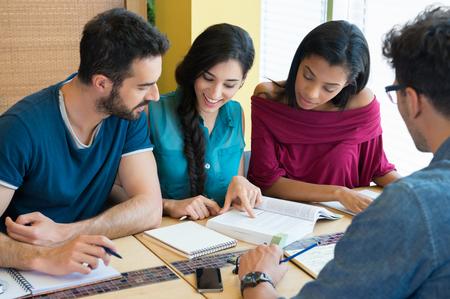 Detailní záběr mladý muž a žena diskutovat na poznámky. Šťastný a usmívající se student studuje v knihovně. Více etnická skupina studuje na knihu pro další zkoušku.