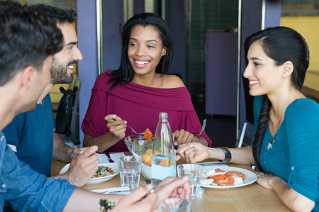 dining table: Closeup shot of young women and men having meal. Friends looking at eachother during the lunch. Smiling young friends eating together at restaurant in a summer day. Stock Photo