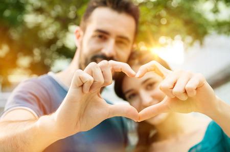 O tiro do close up do homem novo e da mulher que fazem o coração dá forma com mão. Casal apaixonado fazendo formato de coração com as mãos ao ar livre. Mãos femininas e masculinas que compõem a forma do coração.