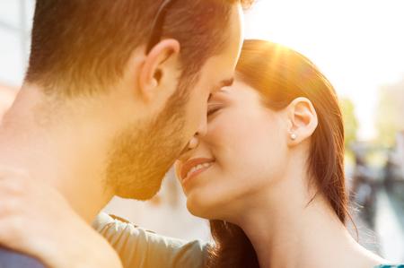 Gros plan d'un jeune couple embrassant l'extérieur. Gros plan d'aimer couple enlacé et en l'embrassant. Faible profondeur de champ avec un accent sur jeune couple baisers.