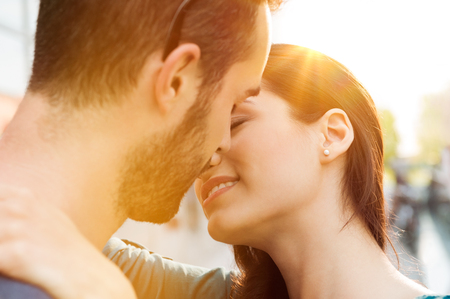 parejas romanticas: Primer disparo de la joven pareja besándose al aire libre. Cierre de amantes de la pareja abrazándose y besándose. Poca profundidad de campo con enfoque en joven pareja besándose. Foto de archivo