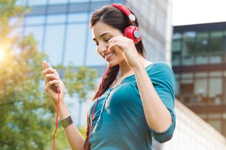 Close-up shot van de jonge vrouw, het luisteren naar muziek met mobiele telefoon buitenshuis. Happy lachende meisje luistert naar muziek met oortelefoon. Portret van zorgeloze vrouw luisteren naar muziek in een centrum van de stad.